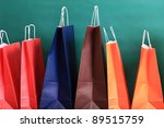 paper Shopping yellow eco orange gift bags on green background ecologocal - stock photo