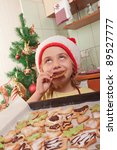girl in santa hat eating Christmas cookies - stock photo
