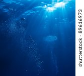 abstract underwater scene sunrays and air bubbles in deep blue sea - stock photo