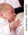 studio-shot of a mother give breast to a newborn baby girl. - stock photo