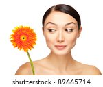 Portrait of beautiful young woman with a flower. Taken in the studio. - stock photo