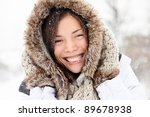 winter woman happy outside in snow smiling joyful on snowing winter day. Cute closeup portrait of beautiful mixed race Caucasian Asian girl cheerful and excited outdoors. - stock photo