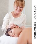 Small photo of Acupuncturist placing needle in ear in auricular acupuncture treatment