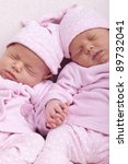 studio-shot of identical ( similar ) newborn babies. twin sisters sleeping and holding hand. - stock photo