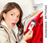 Expensive shopping prices in euro. Woman shopper shocked and surprised over high clothes retail prices in clothing store. Funny image of multicultural young woman. - stock photo