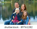 a happy family of four sitting... | Shutterstock . vector #89761282