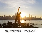 A Woman Runner Stretching In A...