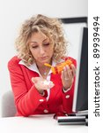 Headache at work - overworked woman taking lots of pills - stock photo