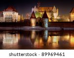 Malbork castle in Poland at night with reflection in Nogat river - stock photo