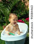 cute funny little boy bathing outdoor on green lawn among flowers - stock photo