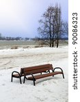 Snowy winter scenery at Wisla river with lonely bench - stock photo