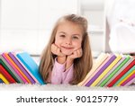 Little girl discovering the colorful world of books and knowledge - stock photo