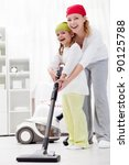 Cleaning up the room together - woman and little girl with vacuum cleaner - stock photo