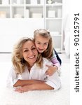 Happy times together - little girl with her beautiful mother laying on the floor - stock photo
