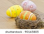 Beautiful eggs in the nest in wood background - stock photo