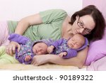studio-shot of a mother with her identical ( similar ) baby  twin girls, resting on a sofa. twins wearing handmade knitted  cardigans. - stock photo