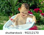cute funny little boy bathing among flower petals outdoor on green lawn - stock photo
