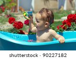 cute funny baby boy bathing outdoor on green lawn among flowers - stock photo