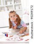 Little artist girl painting a masterpiece kneeling on the floor - stock photo