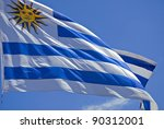 Uruguay flag flames close-up over a clear blue sky background. - stock photo