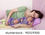 studio-shot of a mother with her identical ( similar ) baby  twin girls, sleeping on a sofa .twins wearing handmade knitted  cardigans. - stock photo