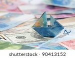Swiss france folded as boat on world currencies - symbol of strong Swiss francs and other currencies with sinking values. - stock photo