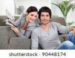 Small photo of Couple relaxing in their living room