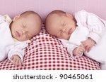 studio-shot a identical ( similar ) baby twin girls sleeping on a pillow. - stock photo