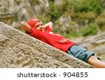 Boy Laying On A Stone Under Th...