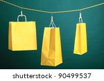 Shopping yellow gift bags on green background - stock photo