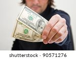 Casual adult man is paying in dollar bills, corruption and bribe concept. - stock photo
