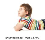 cheerful smiling little boy lying on the floor. Looking to the side into copyspace. Isolated on white background.  shooting in the studio - stock photo