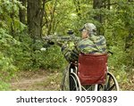 disabled man in wheelchair with a crossbow waiting for action - stock photo