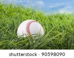 Base ball in grass with blue sky in the background - stock photo