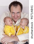 studio-shot of a happy father holding his identical ( similar ) baby twin daughters in his arms. - stock photo