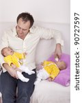 multitasking.  studio-shot of a happy father holding and feeding his identical ( similar ) baby twin daughters in his arms. - stock photo