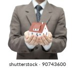 Businessman holding a toy house - stock photo