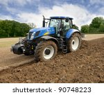 Blue Tractor Plows Field At...