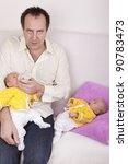 studio-shot of a happy father feeding his identical ( similar ) baby twin daughter in his arm. - stock photo