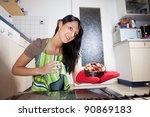 gorgeous woman with a cake seen from inside of a stove - stock photo