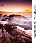 Wave crashes over rocks on Australian beach - stock photo