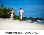 Young couple walking on the beach - stock photo