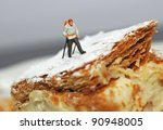 Small hiker figure walking on a piece of cake with castor sugar imitating snow - stock photo