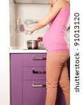 Young pregnant blonde woman cooking in kitchen - stock photo