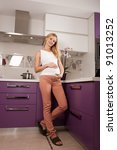 Young pregnant blonde woman in kitchen holding her belly - stock photo