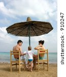family under umbrella on beach | Shutterstock . vector #910247