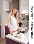 Young pregnant blonde woman with laptop in kitchen - stock photo