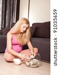 Young pregnant blonde woman sitting on the floor with seashells - stock photo