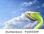 Grunged image of a sunflower seedling against a cloudscape. - stock photo