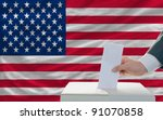 man putting ballot in a box during elections in america - stock photo